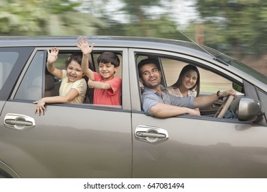 Children with parents waving from car window