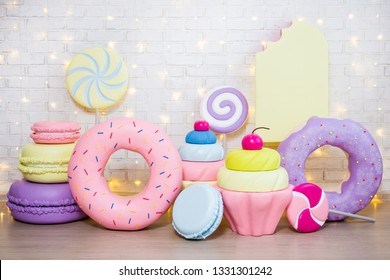 children party background - set of huge artificial sweets and pastry decorations over white brick wall with lights