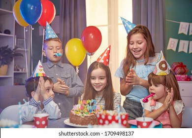 Children in party caps celebrating birthday with cake and balloons at home.