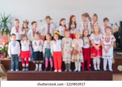 children perform at concert in primary school. Children's theatrical creativity, amateur performance in Kindergarten. Children's creativity. Children's choir in kindergarten. Blurry