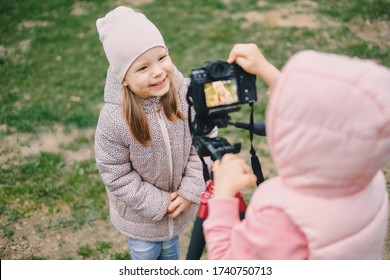 Children with photo camera in a city park. Two girls make a video and photo for the Internet, record a video blog for camera.