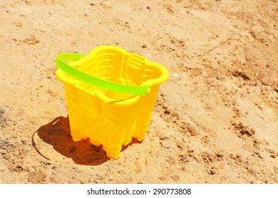 Children plastic bucket on the sand