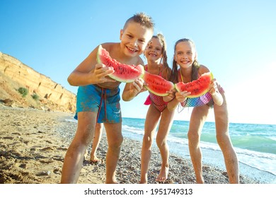 Children play by the sea and eat watermelon. High quality photo.