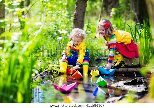 Children play with colorful paper boats in a small river on a sunny spring day. Kids playing exploring the nature. Brother and sister having fun at a forest stream. Boy and girl with toy boat and ship