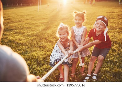 Children play with dad in the park. They pull the rope and have fun laying on a sunny day.