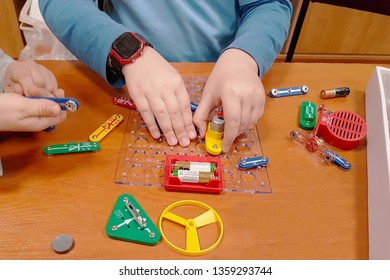 Children play in the electromechanical designer. Education of the younger generation. Electrical circuits. Multi-colored toys for training and development of boys and girls. Physics for beginners.