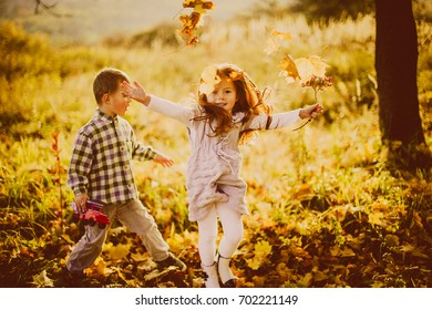 Children play with fallen leaves in the evening