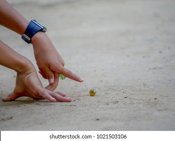 children is play a game of marble,fun,Hand of child playing marbles