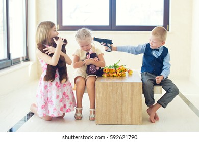 Children play games together in room. Boy attacks girls with fake gun. Difference between toys for male and female.