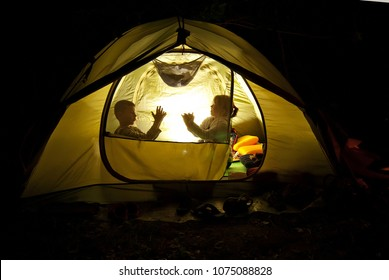 children play in the hike. the tent lights at night from the flashlight. dark silhouettes of children.