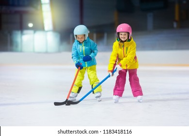 Children play ice hockey on indoor rink. Healthy winter sport for kids. Boy and girl with hockey sticks hitting puck. Child skating. Little kid on sports training after school. Snow and ice fun.