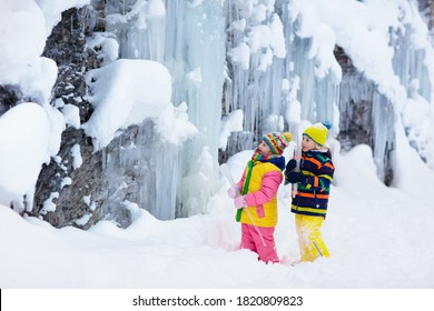 Children play with icicle in snow. Kids lick icicles at frozen mountain waterfall on family Christmas vacation in winter. Outdoor fun in snowy park by cold weather. Kid playing with ice in forest.