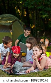 Children play in nature with a laptop. Boys and girls are resting in a tent camp. Children sit on the carpet on the grass in summer.