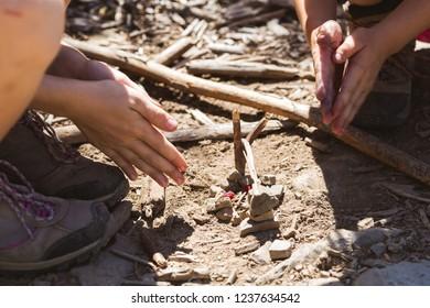children play on a hike - warm their hands around an improvised campfire
