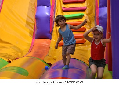 children play on an inflatable trampoline