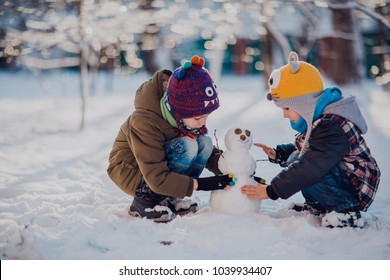 Children play outdoors in snow. Outdoor fun for family Christmas vacation. Two little kid boys in colorful clothes playing outdoors. Happy siblings having fun with snowman