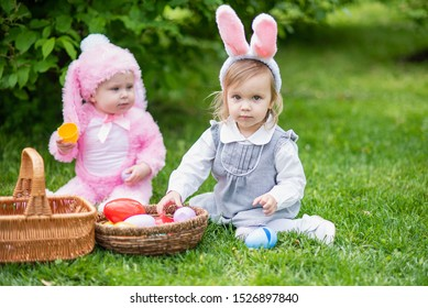 Children play with real rabbit. Laughing child at Easter egg hunt with pet bunny. Little toddler girl playing with animal in garden. Cute funny girl with Easter eggs and bunny ears at garden.