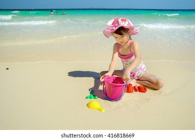 Children play in the sand at the beach. Happy family.Beautiful beaches in the summer of Thailand.Cute girl is relaxing at the beach. Phuket beach. Pattaya beach. Thailand.