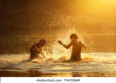 Children play splash water on the river happily.
