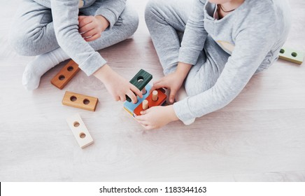 Children play with a toy designer on the floor of the children's room. Two kids playing with colorful blocks. Kindergarten educational games. Close up view.