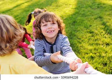 Children play tug of war in the park. Children's Day, June 1, friendship, childhood, vacation, camp