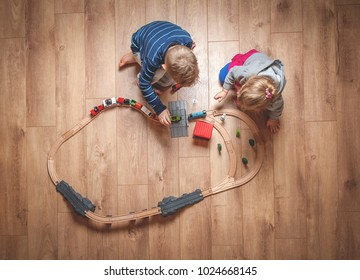 Children play with wooden toy, build toy railroad at home or daycare. Top view of little child playing with toy train. Educational toys for preschool and kindergarten child.