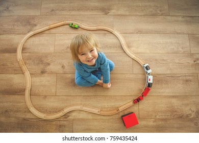 Children play with wooden toy, build toy railroad at home or daycare. Top view of cute little child playing with toy train. Educational toys for preschool and kindergarten child.