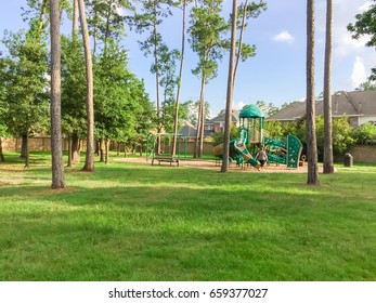 Children playground activities in residential area surrounded by green pine trees, grass lawn at sunset in Humble, Texas, US. Kids run, slide, swing on modern playground. Urban neighborhood concept.