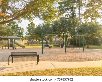 Children playground activities in residential area, long bench surrounded by pine trees, grass lawn sunset in Texas, US. Stairs, slide, swing for kids on modern playground. Urban neighborhood concept