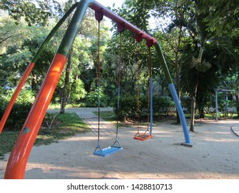 Children playground ayunan swing hanging in park garden. Made of shiny iron chain. Copy space wallpaper blank empty. Enjoy holiday concept. Brown seat board and colorful swinger isolated  on sky view