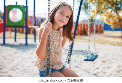 Children playground. Cute little girl having fun with swing in the park