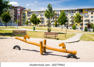 Children playground in nature in front of row of newly built block of flats