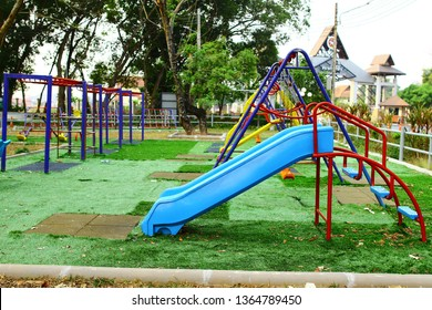 Children playground on yard activities in public park surrounded by green trees at sunlight morning. Children run, slide, swing,seesaw on modern playground. Urban neighborhood childhood concept -