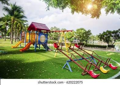 Children playground on yard activities in public park surrounded by green trees at sunlight morning. Children run, slide, swing,seesaw on modern playground. Urban neighborhood childhood concept.