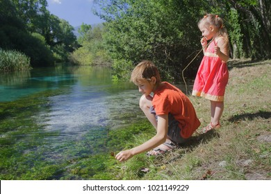 Children playing active game on Tirino river bank in Italian Abruzzo province