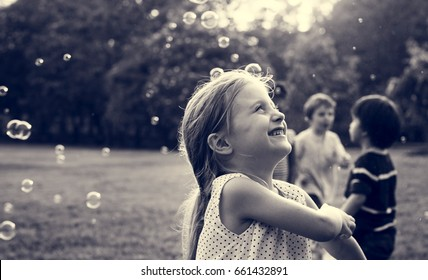 Children is playing bubbles in a park