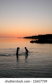 Children playing in calm Caribbean at sunset.