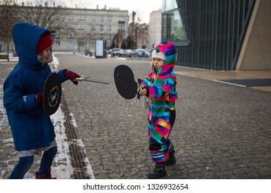 Children playing with cardboard swords outdoors, Warsaw, Poland