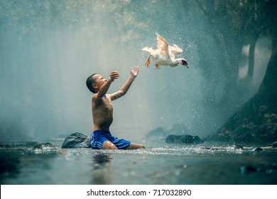 Children playing catch with duck in river