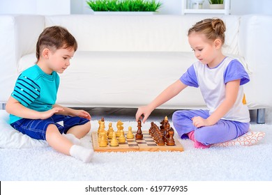 Children playing chess at home. Games and activities for children. Family concept.