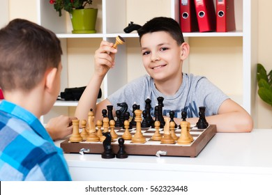 Children playing chess at the table. the concept of childhood and board games, brain development and logic