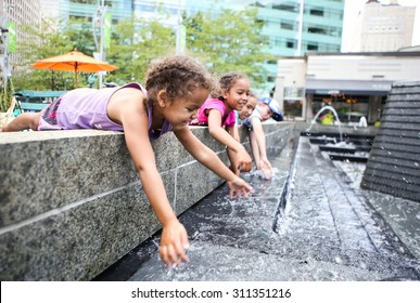 Children playing in a city fountain. Shallow focus on girl's face.