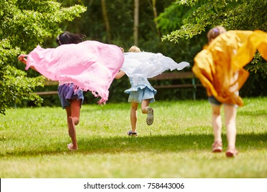 Children playing with cloth and running in the park making waves