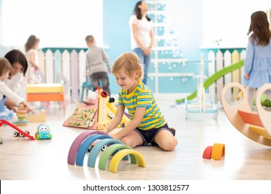 Children playing with colorful blocks. Kindergarten educational games.