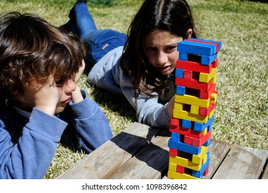 Children playing colorful jenga game lying on green grass on their yard in bright sunlight on summer day.
