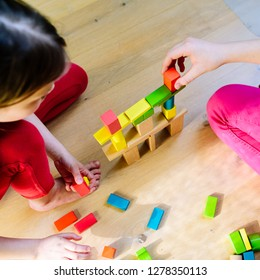 children playing with colorful wooden blocks - view from above