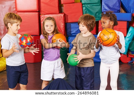 Children playing with different balls in gym of preschool