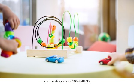 Children playing with different toys near wire bead maze. Bright tiny toy cars in the foreground. Kindegarten activities concept