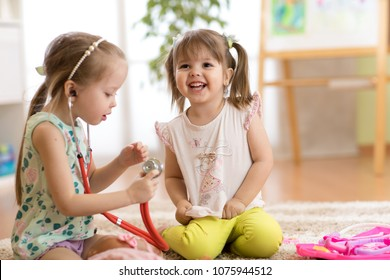 Children playing doctor in kindergarten, playschool, daycare center or home