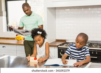 Children playing and drawing in the kitchen at home